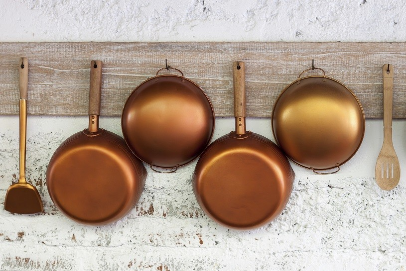 Copper kitchen utensil on the white painted brick wall