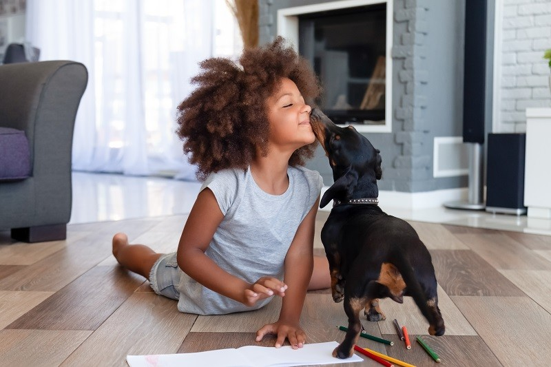 girl and dog playing on family friendly flooring